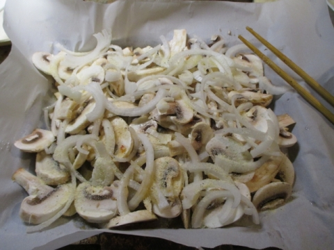 Cover fish with sliced mushrooms and onion rings and start sprinkling some galic spread