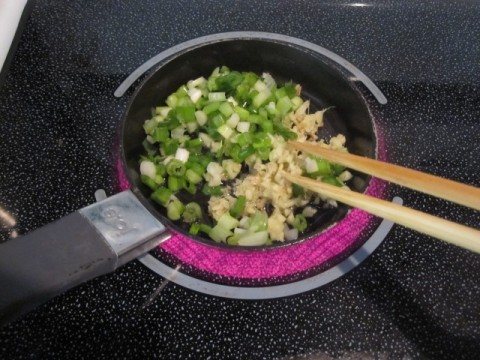 Heating minced ginger and chopped scallion in oil