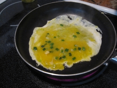 Spread the egg mixture in the pan to form a thin layer of egg